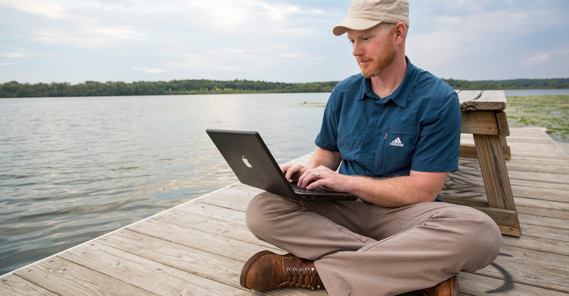 Man working on Laptop while sitting on the pier at Lake Wingra.