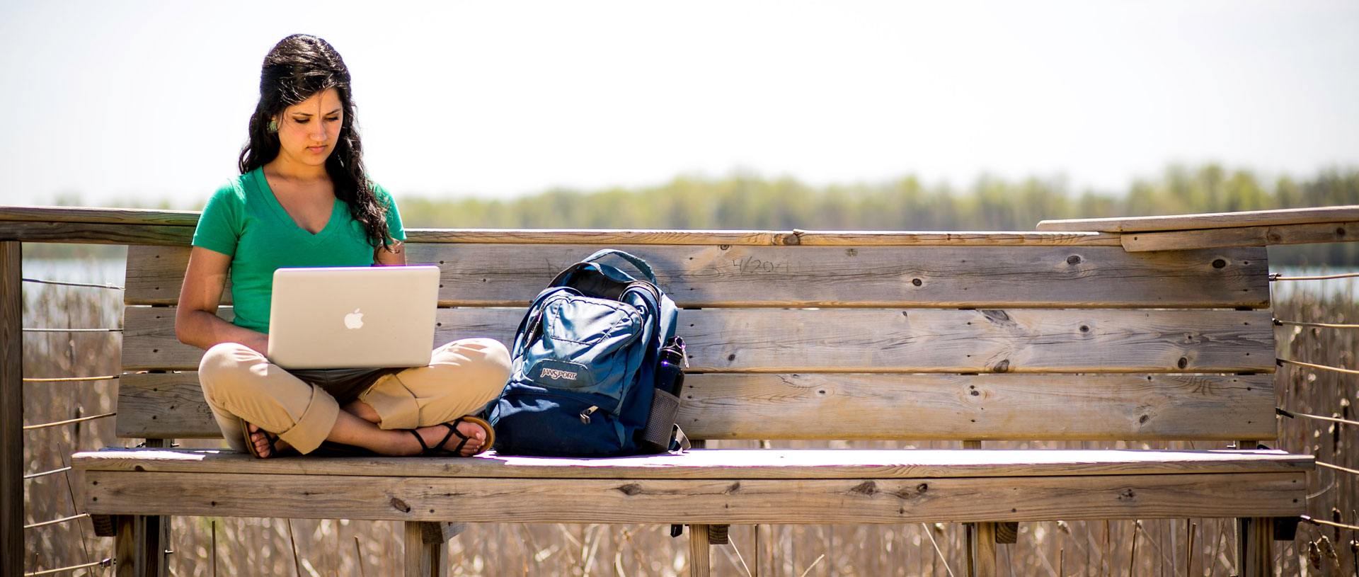 Undergrad female studying by the lake.