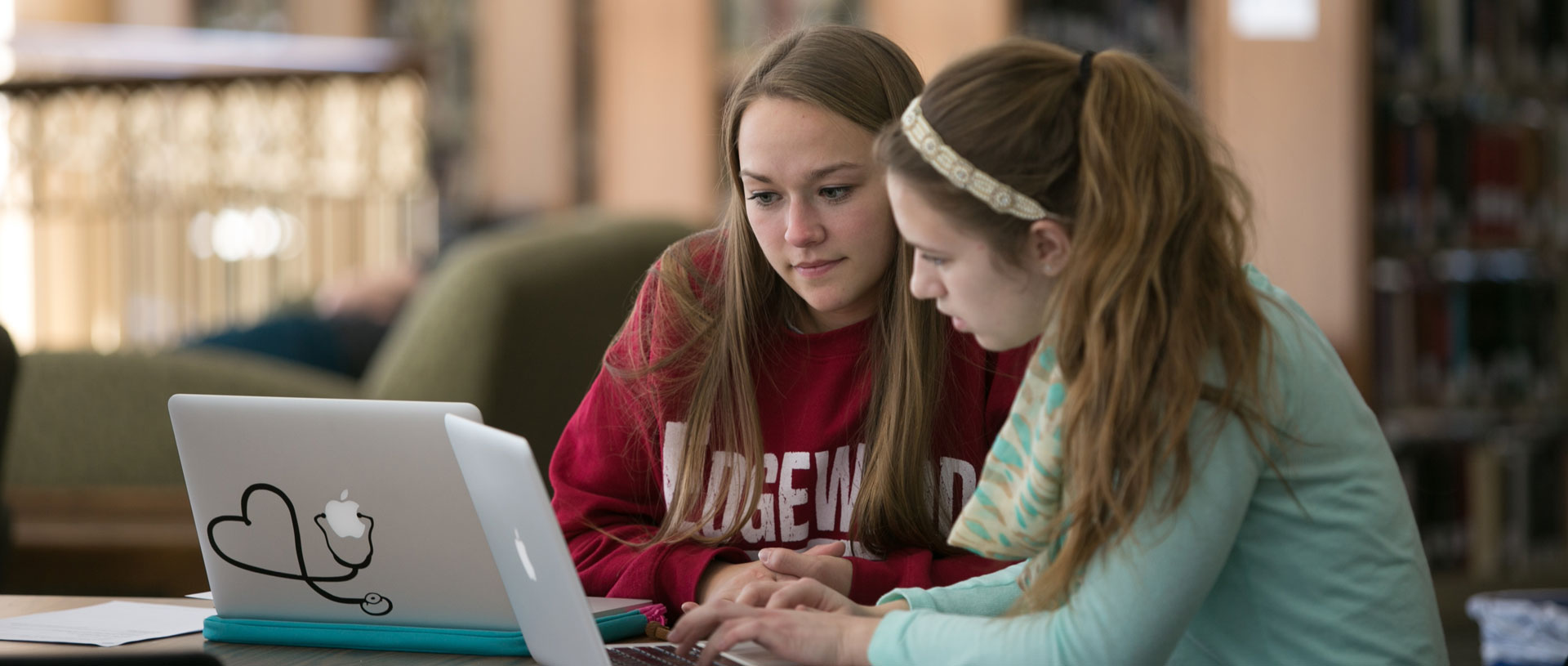 Undergrad females studying in the Library.