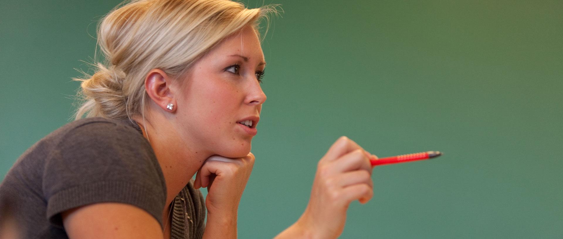 Female undergrad student engaging in class.