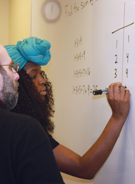 Student solving math problems on a white board.